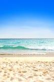 Playa arenosa hermosa contra el cielo azul Fotos de archivo