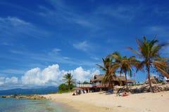 Playa arenosa tropical con la bandera cubana y una casa cubana tradicional rodeada por las palmeras, Ancon de Playa, Trinidad, Cu fotos de archivo