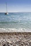 Playa arenosa y velero blancos Fotos de archivo