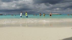 Playa asombrosa de la arena con agua pura y la gente que se divierten, Bahamas metrajes