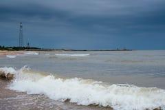 Playa blanca de la arena con las ondas y cielo azul en día de verano frío Fotografía de archivo libre de regalías