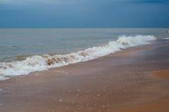 Playa blanca de la arena con las ondas y cielo azul en día de verano frío Foto de archivo