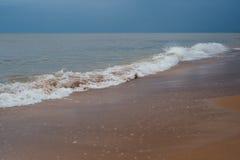 Playa blanca de la arena con las ondas y cielo azul en día de verano frío Imagen de archivo libre de regalías