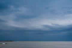 Playa blanca de la arena con las ondas y cielo azul en día de verano frío Imágenes de archivo libres de regalías