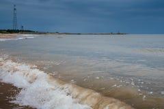 Playa blanca de la arena con las ondas y cielo azul en día de verano frío Fotos de archivo