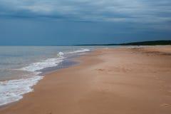 Playa blanca de la arena con las ondas y cielo azul en día de verano frío Imagenes de archivo