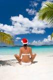 Playa blanca del sombrero de la Navidad del bikiní de la mujer Imagen de archivo libre de regalías