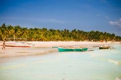 Playa blanca tropical de la arena con las palmeras verdes y los barcos de pesca parqueados en la arena Paraíso exótico de la isla Foto de archivo libre de regalías