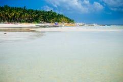Playa blanca tropical de la arena con las palmeras verdes y los barcos de pesca parqueados en la arena Paraíso exótico de la isla Imagen de archivo libre de regalías