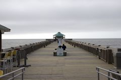 Playa Carolina del Sur de la locura, el 17 de febrero de 2018 - mujer que se sienta solamente en banco del paseo marítimo en día  Fotografía de archivo