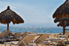 Playa, ciudad y vista al mar en Puerto Vallarta México con las sillas de playa y la costa costa Foto de archivo