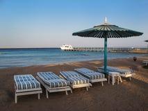 Playa con cuatro sillas y paraguas Fotos de archivo