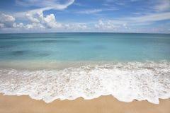 playa con el aerosol blanco de la onda Fotografía de archivo