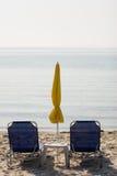 Playa con el deckchair Imagenes de archivo