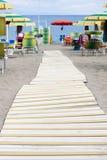 Playa con el paraguas y el paseo marítimo Fotos de archivo