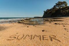 Playa con el verano de la palabra escrito en arena Imágenes de archivo libres de regalías