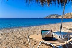 Playa con la computadora portátil Imágenes de archivo libres de regalías