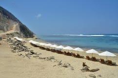 Playa con la roca, la colina y las sillas Fotografía de archivo