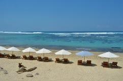 Playa con la roca y las sillas Foto de archivo