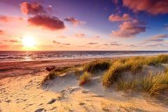 Playa con las dunas de arena en la puesta del sol fotos de archivo