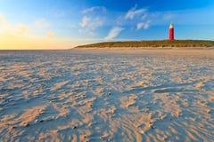 Playa con las dunas de arena y el faro en la puesta del sol foto de archivo
