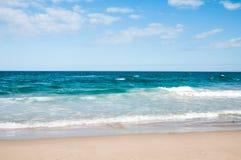 Playa con las ondas en un día soleado Fotografía de archivo