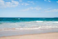 Playa con las ondas en un día soleado Fotografía de archivo libre de regalías
