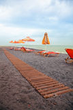 Playa con las sillas y la calzada del sol Fotos de archivo
