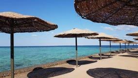 Playa con las sombrillas de la cubierta, paraguas Playa, mar, arena, onda Océano y paraíso hermoso de la playa, cielo azul, nubes almacen de video
