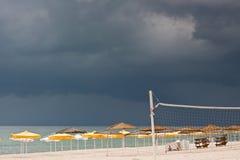 Playa con los deckchairs y el mar de los parasoles Imagenes de archivo