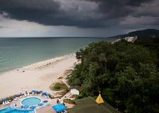 Playa con los deckchairs y el mar de los parasoles Imagen de archivo libre de regalías