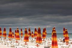 Playa con los deckchairs y el mar de los parasoles Fotos de archivo libres de regalías