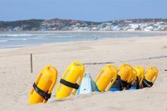 Playa con los dispositivos de flotación salvavidas Foto de archivo libre de regalías
