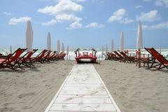 Playa con los paraguas y las sillas Imagenes de archivo