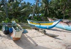 Playa con los pequeños barcos de madera ligeros coloridos Imagenes de archivo