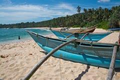 Playa con los pequeños barcos de madera ligeros coloridos Fotos de archivo libres de regalías