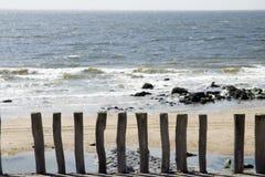 Playa con los postes de madera Foto de archivo libre de regalías