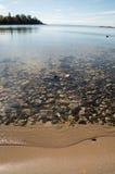 Playa cristalina del lago Superior con la arena y las rocas Fotos de archivo