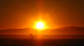 Playa Dawn. A lone cyclist rides through the desert as the sun rises over the Nevada mountains at the Burning Man festival Royalty Free Stock Image