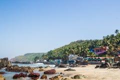 Playa de Arambol con las piedras, las palmas y las casas, Goa, la India Foto de archivo libre de regalías