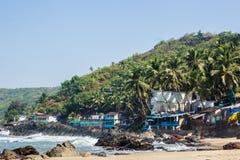 Playa de Arambol con las piedras, las palmas y las casas, Goa, la India Imagenes de archivo