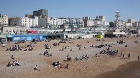 Playa de Brighton ocupada con los turistas y los visitantes el festivo en la opinión hermosa de la cacerola del tiempo