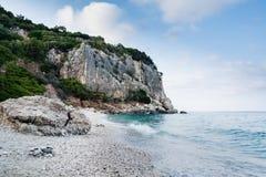 Playa de Cala Gonone en Cerdeña con las rocas en un verano cubierto fotografía de archivo