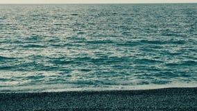 Playa de guijarros redondos multicolores, y el chapoteo de ondas saladas almacen de video