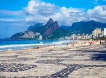 Playa de Ipanema con el mosaico de la acera y de la montaña Dois Irmao dos Brother en Rio de Janeiro imagen de archivo libre de regalías