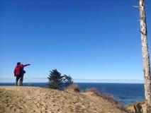 Playa de Kiwanda Oregon con señalar del cielo azul y de la gente fotografía de archivo