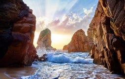 Playa de la arena entre rocas en puesta del sol de la tarde Fotografía de archivo