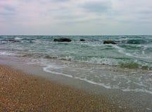 Playa de la arena y rocas costeras Foto de archivo libre de regalías