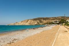 Playa de la bahía de Pissouri con los turistas que se relajan en un día soleado caliente, Chipre Imagen de archivo