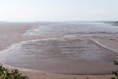 Playa de la marea baja en la bahía de Fundy Nuevo Brunswick - el agua de color marrón de Canadá llamó el río del chocolate Imagen de archivo libre de regalías